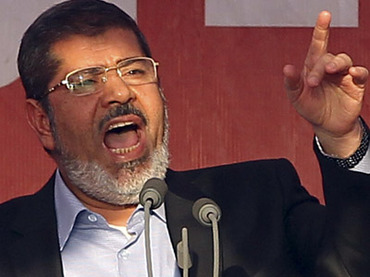 Egypt's Islamist President-elect Mohamed Mursi delivers a speech while surrounded by his body guards in Cairo's Tahrir Square