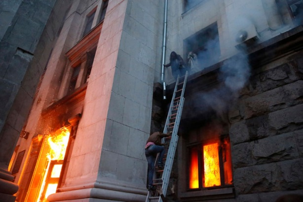 People wait to be rescued on the second storey's ledge during a fire at the trade union building in Odessa