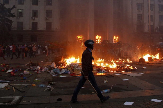 A protester wearing a Ukrainian flag walks past a burning tent camp and a fire in the trade union building in Odessa
