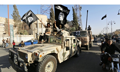 Isis fighters drive a US-made Humvee  along the streets of Syria's northern Raqqa province