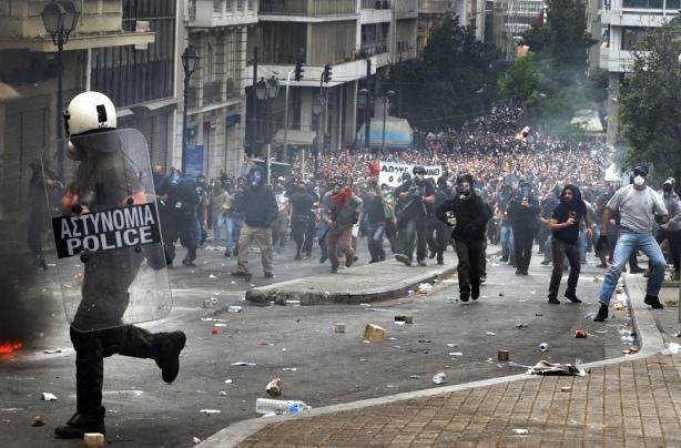 A Greek riot police officer runs to esca