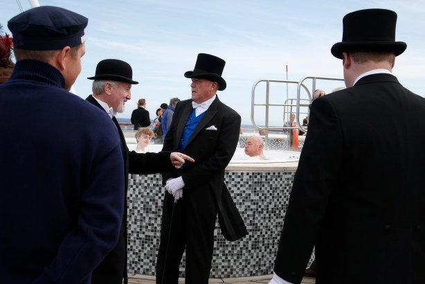 Passengers wearing period dress arrive on the aft deck for a final group photograph on board the Titanic Memorial Cruise in the Atlantic Ocean off Cape Cod