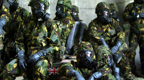 British Royal Air Force personnel wait in a bunker wearing full Nuclear Biological and Chemical suits after a warning of a Scud missile attack on their base in Kuwait March 20, 2003. Iraq fired Scud missiles at Kuwait on Thursday, officials said, sending U.S. troops scrambling into chemical protective suits and setting air raid sirens blaring in Kuwait City. - RTXLV2B