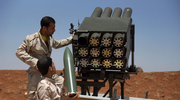 Free Syrian Army fighters prepare a rocket launcher prior to firing it towards forces loyal to Syria's President Bashar al-Assad in Izra'a in Deraa countryside