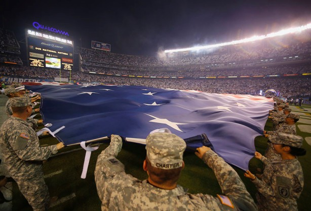 California National Guard members hold out a giant American flag before the start of the Monday Night NFL football game between the Houston Texans and the San Diego Chargers  in San Diego, California  September 9, 2013.  REUTERS/Mike Blake   (UNITED STATES - Tags: SPORT FOOTBALL MILITARY) - RTX13FAR