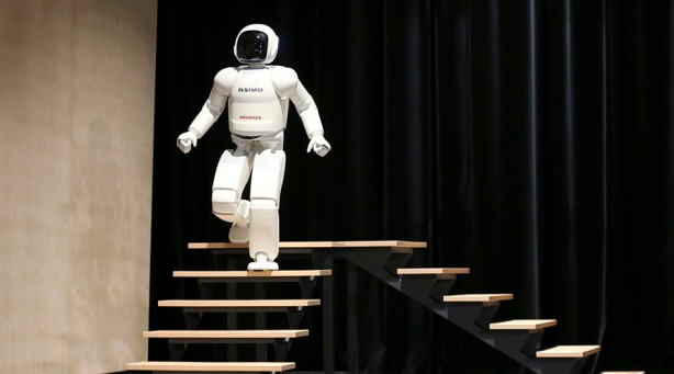 Honda's latest version of the Asimo humanoid robot walks down stairs during a presentation in Zaventem near Brussels July 16, 2014. Honda introduced in Belgium an improved version of its Asimo humanoid robot that it says has enhanced intelligence and hand dexterity, and is able to run at a speed of some 9 kilometres per hour (5.6 miles per hour).  REUTERS/Francois Lenoir (BELGIUM - Tags: SCIENCE TECHNOLOGY BUSINESS SOCIETY) - RTR3YVL3