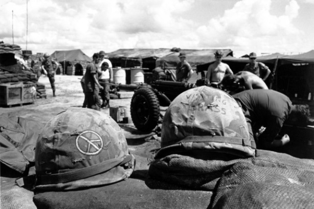 Members of the B battery, 2nd battalion, 321st Brigade, 82nd Airborn Division clean a 105mm Howlitzer in Saigon on Sept. 16, 1969. A couple of army helmets atop a sandbag wall are decorated with a peace sign, a symbol popular with this war. (AP Photo/Godfrey)