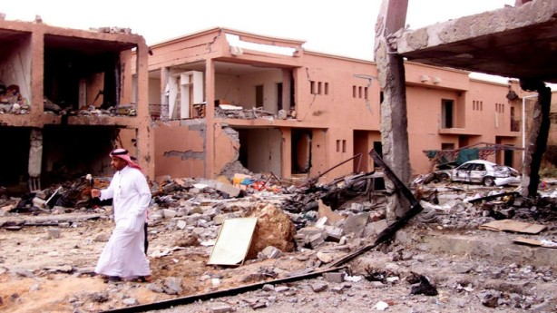 A SAUDI SECURITY MAN WALKS IN FRONT OF A DAMAGED BUILDING IN RIYADH FOLLOWING BOMB BLAST.