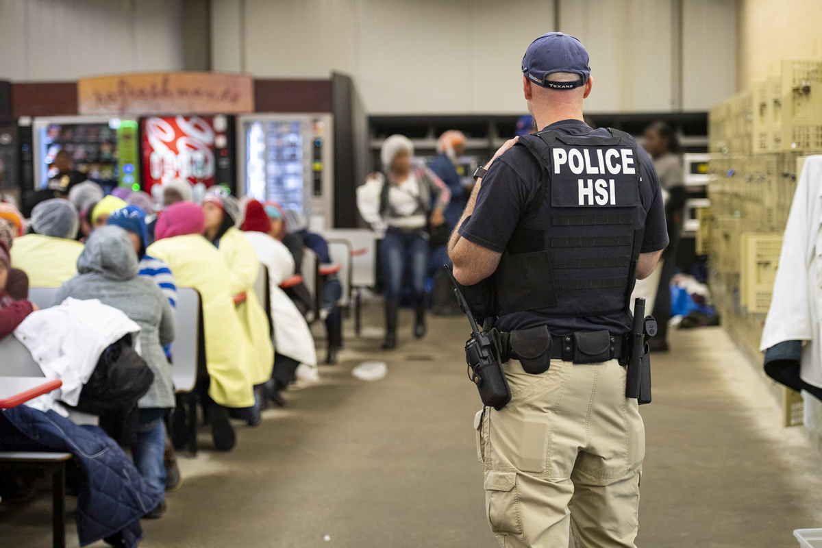 FILE PHOTO: Homeland Security Investigations (HSI) officers from Immigration and Customs Enforcement (ICE) look on after executing search warrants and making some arrests at an agricultural processing facility in Canton